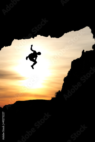 silhouette of man jumping of rock