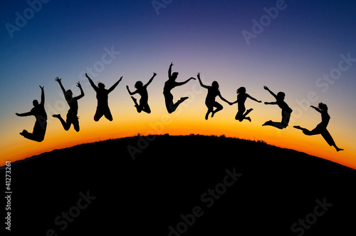 silhouette of teens jumping on hill