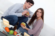 Young couple eating burgers on sofa