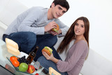 Young couple eating burgers on sofa