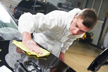 mechanic repairing and polishing car headlight