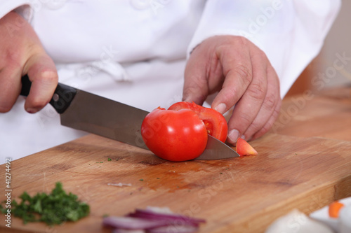 Cook cutting a tomato
