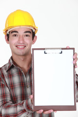 Young construction worker holding up a blank clipboard