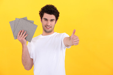 Man holding tiles on yellow background