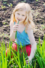 little girl eats green onions