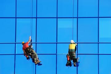 Two wahsers wash facade windows