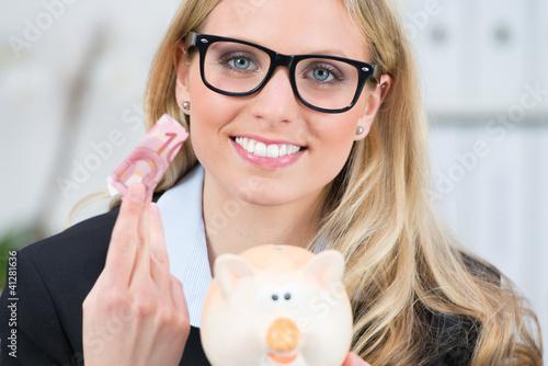 junge frau wirft 10 euro ins sparschwein