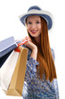 Long haired female holding paper-bags with purchases and wear a