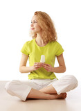 Woman with energy-saving bulb sitting cross-legged on floor.