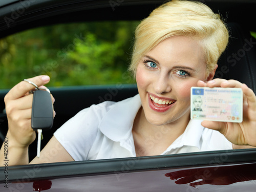 Woman sitting in car is happy getting a driver licence