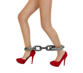 Slim woman legs in red high heels shoes with shackles
