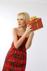 Beautiful blonde girl holding christmas gift in red dress