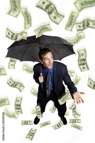 Raining money on a businessman with umbrella