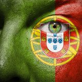 Flag painted on face with green eye to show portugal support