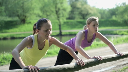 Two young women doing push-ups at the park