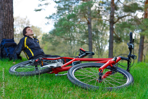 Red Bike Lying on Green Grass. Cyclist Relaxes in the background