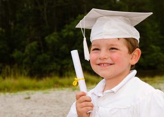 Young boy with cap and gown and certificate for graduation