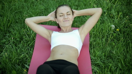Woman in sport outfit doing sit ups in a park