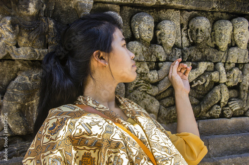 Indonesian girl touching ancient releif in Borobodur