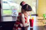 Child girl drinking strawberry smoothie