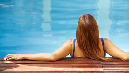 Entspannte Frau im Pool von hinten