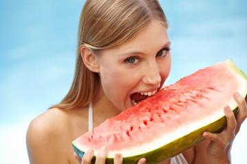 Junge Frau beißt in Melone