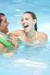 Lachende Frau und Mann mit Schwimmring
