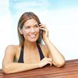 Frau mit Handy am Pool