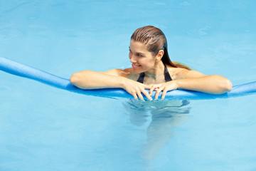 Frau mit Schwimmnudel im Wasser
