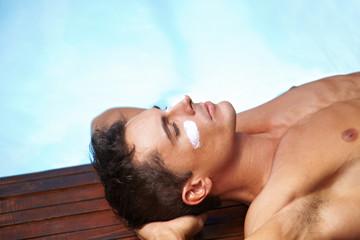Mann mit Sonnencreme sonnt sich