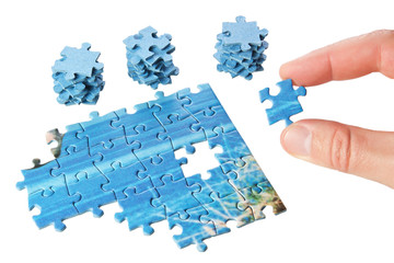 The missing puzzle in the fingers on a white background.