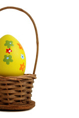 Yellow Easter egg into a basket