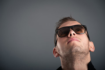 Young boy with sunglasses looking up against grey background.