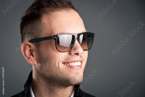 Young boy with sunglasses against grey background.