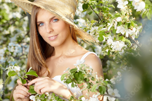 portrait of young lovely woman in spring flowers over amazing ga