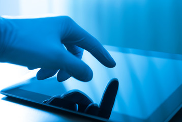 Doctor touching on digital tablet screen