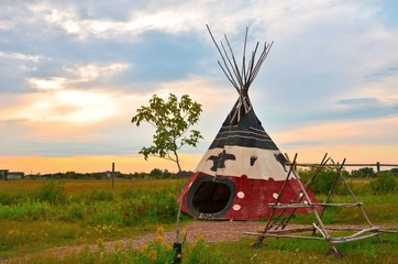 image of an aboriginal tee-pee at sunset in the summer