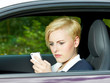 Girl sitting in her car surfs with smartphone on the internet