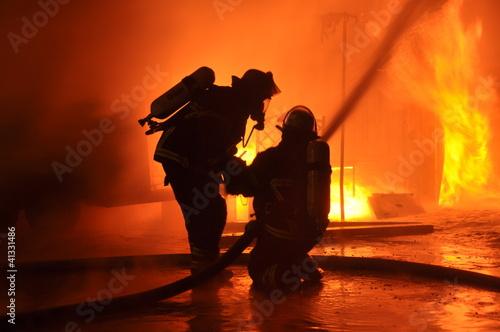 Leinwanddruck Bild Feuerwehr vor Flammenwand