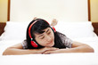 Beautiful Asian woman listens to a music on bed