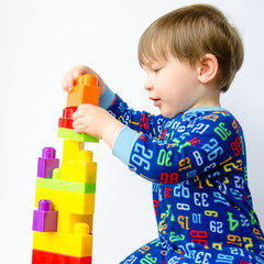 Cute baby boy plays with colorful blocks