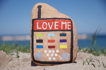 stone mobile phone on the sand, love me concept