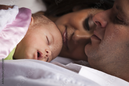 Mixed Race Young Family Laying with Newborn Baby