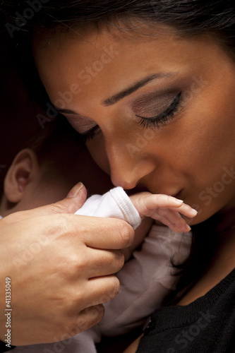 Ethnic Woman Kisses Her Newborn Baby Hand
