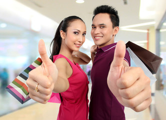 couple with shopping bags showing thumb up