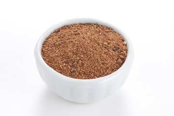 Nutmeg powder (Myristica fragrans) in a white bowl on white back
