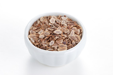 Fennel seeds (Anethum graveolens) in a white bowl on white backg