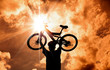 The Silhouette of mountain biker raised bicycle