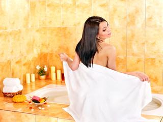 Woman relaxing in bathroom.