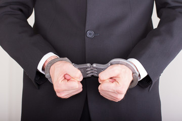Man with handcuffs, business suit, focus on the handcuffs